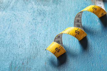Measuring tape on wooden background, closeup. Tailoring equipment