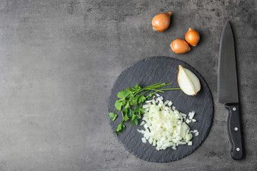 Slate plate with fresh chopped onion on table, top view