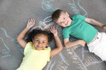 Little children lying near chalk drawing on asphalt, top view