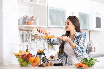 Young woman preparing tasty healthy smoothie at table in kitchen
