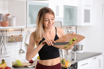 Young woman preparing tasty healthy smoothie in kitchen