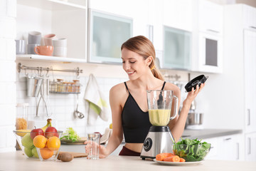 Young woman with tasty healthy smoothie at table in kitchen