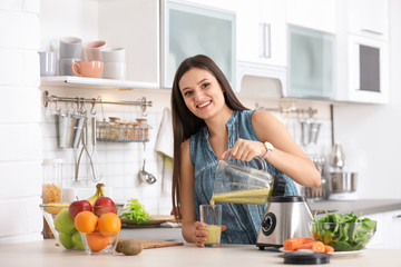 Young woman pouring tasty healthy smoothie into glass at table in kitchen