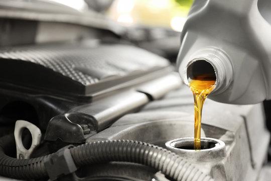 Pouring oil into car engine, closeup