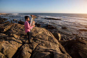 Musician play to Tuba musical instrument on romantic rocky sea shore.