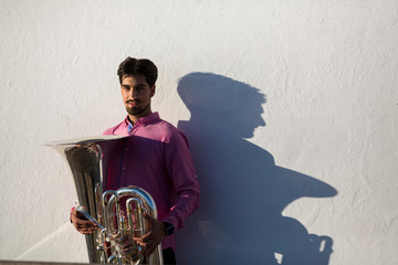 Man with Tuba musical instrument near the white wall the shadow of the tool.