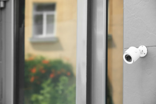 Modern security CCTV camera on wall outdoors