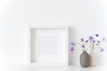 White square portrait frame mockup with spring bellflowers in vases near white wall on white background. Empty frame mock up for presentation design. Template framing for modern art.
