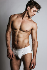 Male model with perfect body in white underwear posing over grey background. Close-up. Studio shot.