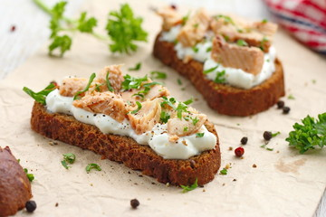 Sandwich with smoked salmon, cream cheese, spices and greens