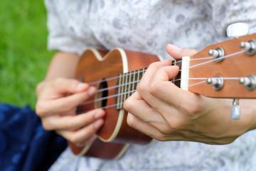 Closeup young woman play on brown ukulele guitar.