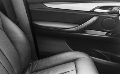 Door handle with Power window control buttons of a luxury passenger car. Black leather interior of the luxury modern car. Modern car interior details. Car detailing