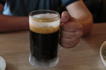 Dark beer in a sweaty mug on wooden table in a hot day.