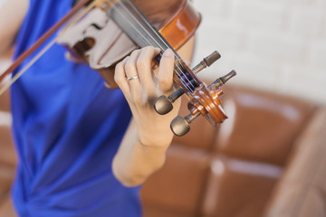 Beautiful young woman in blue dress playing the violin in living room