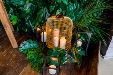 Place for photos made of greenery, yellow lamps, bird cage with candles and a ladder