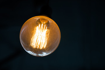 hang Round yellow light lamp or lantern on dark background with copy space. idea and creativity.