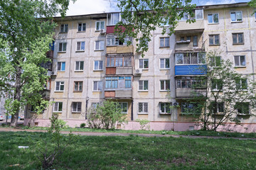 Old apartment house on green meadow, Komsomolsk-on-Amur, Russia