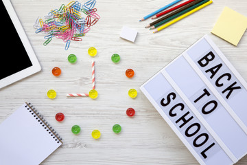 Education concept. Nine o'clock on watch. Clock made of colorful candies, 'back to school' word on lightbox, accessories for study over white wooden background, top view. Flat lay, overhead.