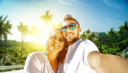 Two young lovers on summer trip and background with palms and sun light.
