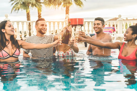 Happy friends cheering with champagne in pool party at sunset