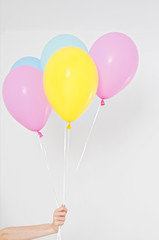 Hand holding balloons. Holiday concept. Colorful party balloons background. Isolated on white. Copy space