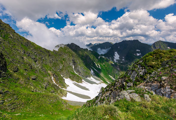 cliffs in the valley of Fagaras mountains. lovely summer scenery on a cloudy day. spots of snow on grassy hillside. beautiful landscape of Romania
