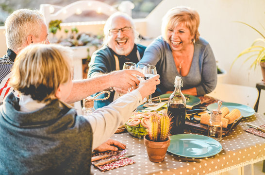 Group of happy senior friends cheering at barbecue meal in terrace outdoor