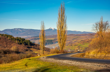 new asphalt road in to the mountains. Pikui mountain with snowy top in the distance. beautiful sunny weather in late autumn. location Volovets serpentine, TransCarpathia, Ukraine