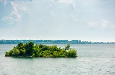 island on the lake zemplinska sirava. beautiful landscape of Slovakia. calm summer day with beautiful cloudscape on the sky. lovely minimalist background