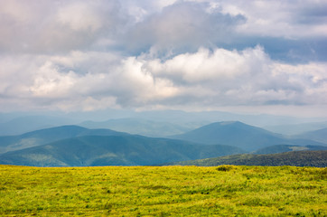grassy alpine meadow in cloudy weather. beautiful landscape of Carpathian mountain in the distance. gorgeous cloud formation above. lovely flat minimalist scenery in summer