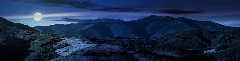beautiful panorama of mountain ridge at night in full moon light. wonderful landscape in early autumn