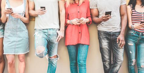 Group of millennial friends watching smart mobile phones