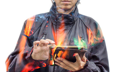 Double exposure of women using tablet with fire burning