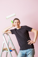 Photo of man with paint roller next to ladder