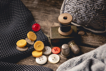 Close-up of wooden sewing spool and buttons set on wooden table