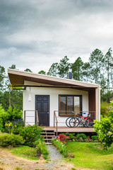 Rustic house with two bycicles and flowers in the garden