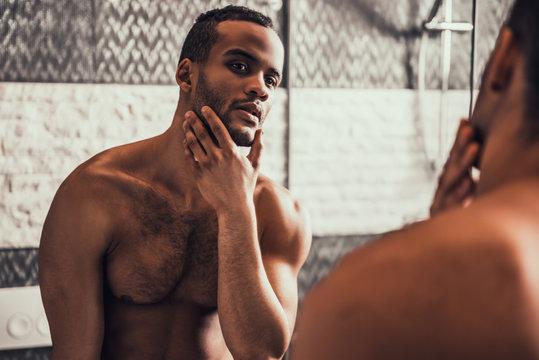 Afro-American Man Looking into Mirror in Bathroom.