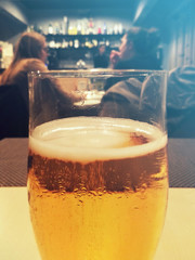 beer with blurred people on background, vertical picture of alcoholic beverage