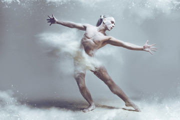 Dancing in flour concept. Naked muscle man dancer in dust / fog. Guy wearing white shorts making dance element stretching his arms in flour cloud on isolated background