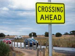 Warning sign of crossing erected with cars driving through a narrow flooded road in distance. Altona, Melbourne VIC Australia.