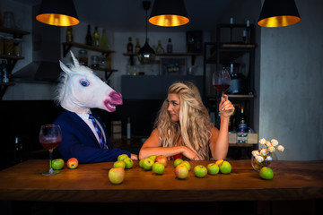 Obraz Unusual couple spend time together at the bar counter in stylish apartments with wine and food. Beautiful girl relaxing with funny boyfriend in comical mask. Unicorn in suit with young woman - fototapety do salonu