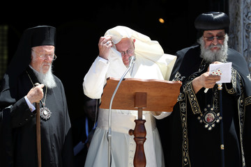 Pope Francis adjusts his shoulder cape after it was blown by a gust of wind after a meeting with Patriarchs of the churches of the Middle East at the St. Nicholas Basilica in Bari