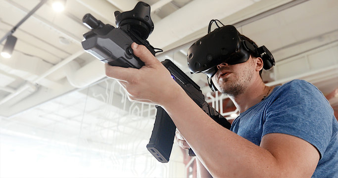Guy playing VR sniper game with virtual reality gun and glasses