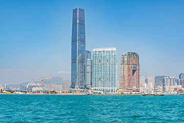 Day view of a harbour and Kowloon peninsula.