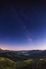 Night landscape with colorful Milky Way and yellow light at mountains.