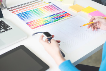 interior design or graphic designer renovation and technology concept - woman working with colour samples for selection. at workplace choosing colour swatches, closeup. Creative people.