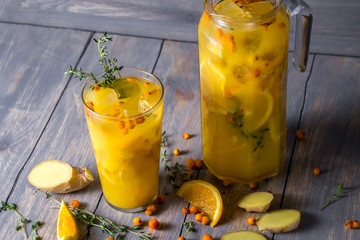 cocktail glass with orange juice, lemon, ginger, thyme and sea buckthorn on wooden background