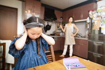 母親に敷かれて耳をふさぐ女の子