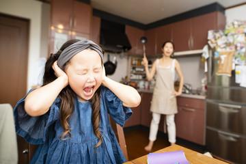 母親に叱られて耳をふさぐ女の子