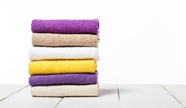Stack of bath towels on light wooden table and white background